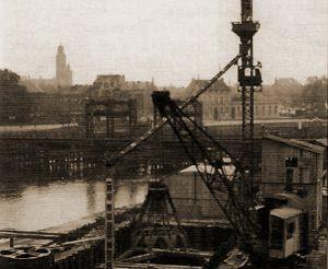 In 1933 werd begonnen met de werkzaamheden aan de nieuwe Veerbrug met op de achtergrond de oude Duitse noodbrug en de toren van het Belfort van Dendermonde. Foto genomen vanaf linker Schelde-oever stroomopwaarts.
