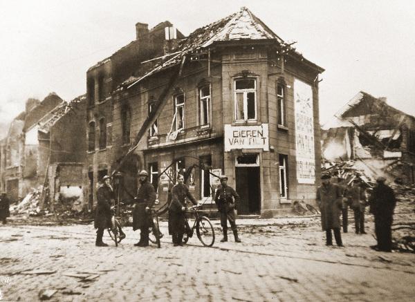 Na de zware luchtaanval op de Tiensepoort kijken een aantal militairen van het II/6J en enkele burgers doelloos rond.